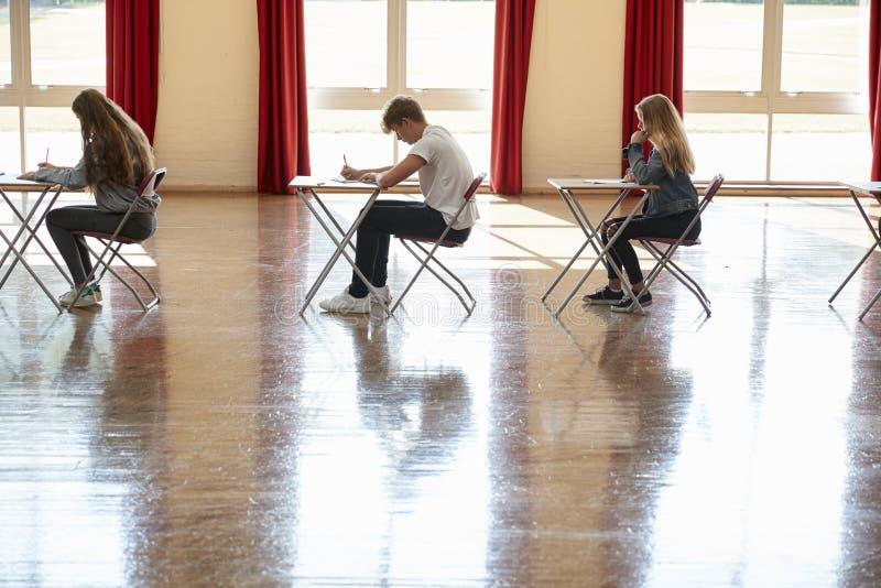Gruppe Jugendstudenten, die Prüfung in der Schule Hall sitzen lizenzfreie stockbilder