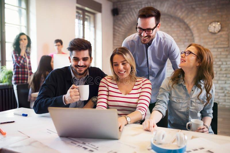 Gruppe junge Architekten, die an Laptop arbeiten stockfotografie