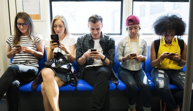 Gruppe junge erwachsene Freunde, die Smartphones in der U-Bahn verwenden stockfoto