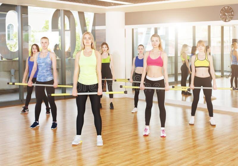 Gruppe junge Frauen in der Eignungsklasse, bildend mit Gewichten aus lizenzfreie stockfotografie