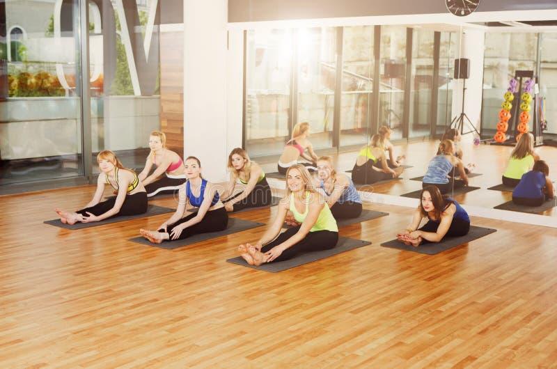 Gruppe junge Frauen in der Yogaklasse, dehnend aus stockbild