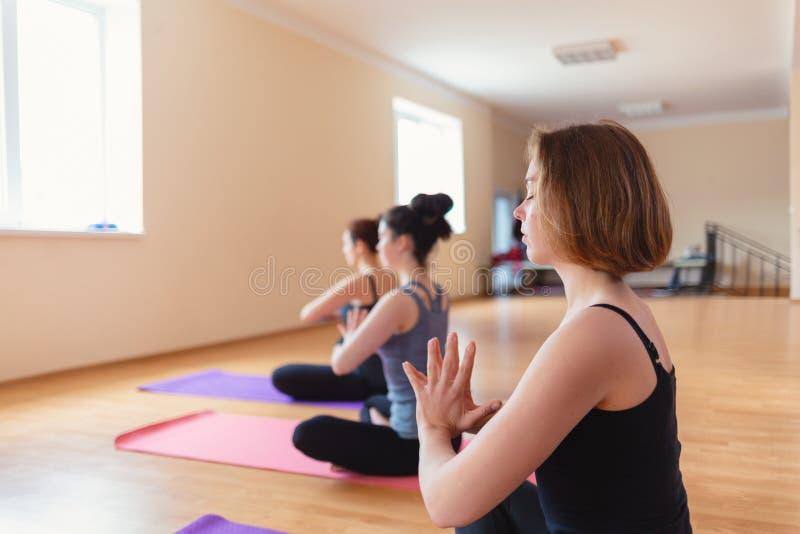 Gruppe junge Frauen, die Meditation in der Yogaklasse tun lizenzfreie stockbilder