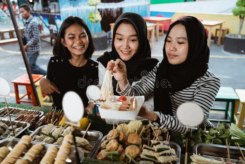 Gruppe junge Frauen an einem Straßennahrungsmittelrestaurant lizenzfreie stockfotos