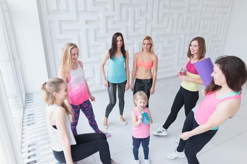 Gruppe junge Frauen mit einem Baby, das einen Chat nach einer Eignungstanzklasse hat stockbilder