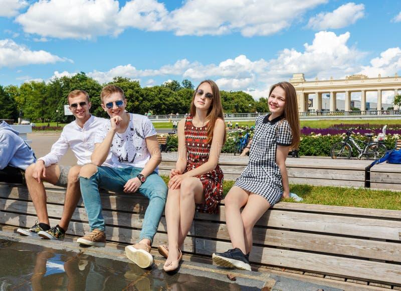 Gruppe junge Freunde, die auf einer Parkbankunterhaltung sitzen stockfotografie