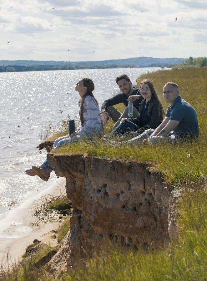 Gruppe junge Freunde, die auf am Rand eines Hügels Erholung draußen genießend sitzen lizenzfreie stockfotos