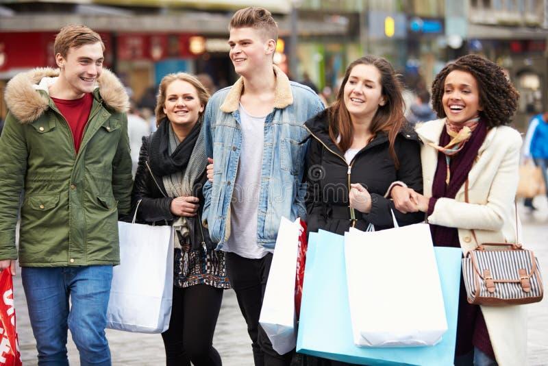 Gruppe junge Freunde, die draußen zusammen kaufen lizenzfreies stockbild