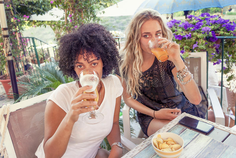 Gruppe junge Freunde, die Snäcke und das Trinken essen stockfotografie