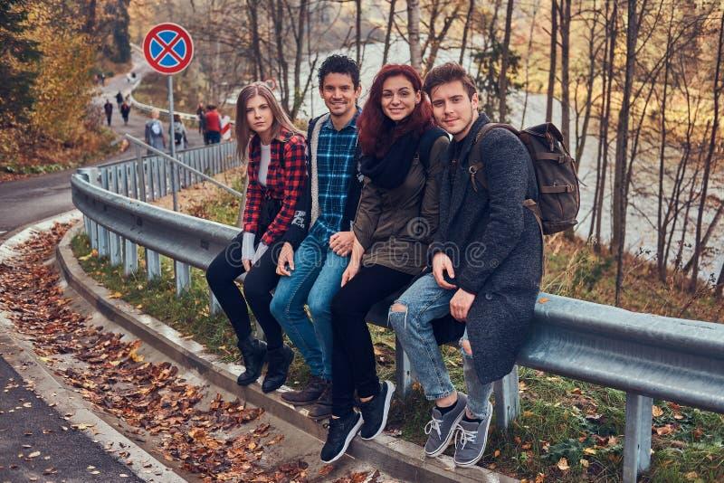 Gruppe junge Freunde mit den Rucksäcken, die auf Leitschiene nahe Straße mit einem schönen Wald und einem Fluss im Hintergrund si stockfotografie