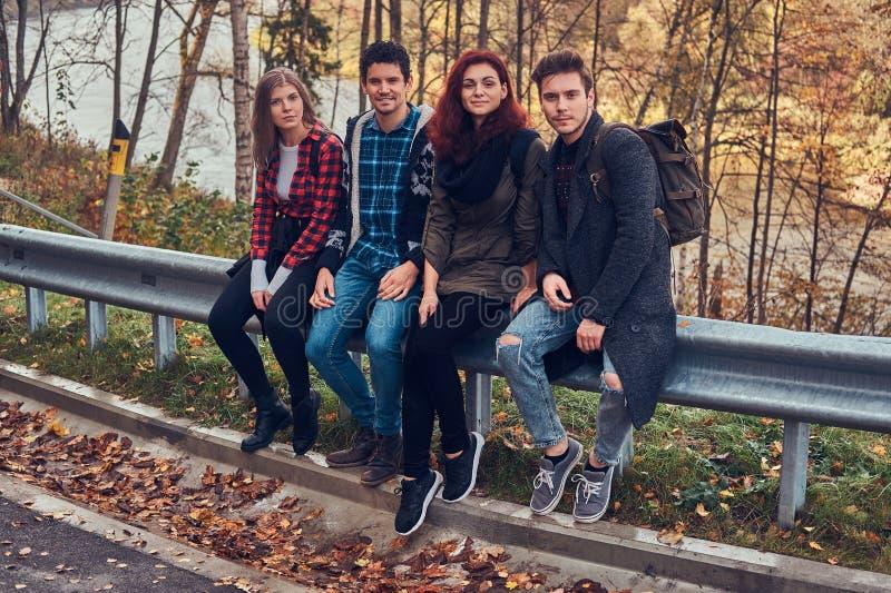 Gruppe junge Freunde mit den Rucksäcken, die auf Leitschiene nahe Straße mit einem schönen Wald und einem Fluss im Hintergrund si lizenzfreies stockbild