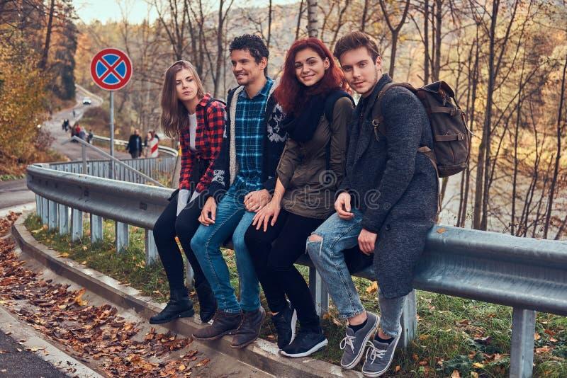 Gruppe junge Freunde mit den Rucksäcken, die auf Leitschiene nahe Straße mit einem schönen Wald und einem Fluss im Hintergrund si stockfotos