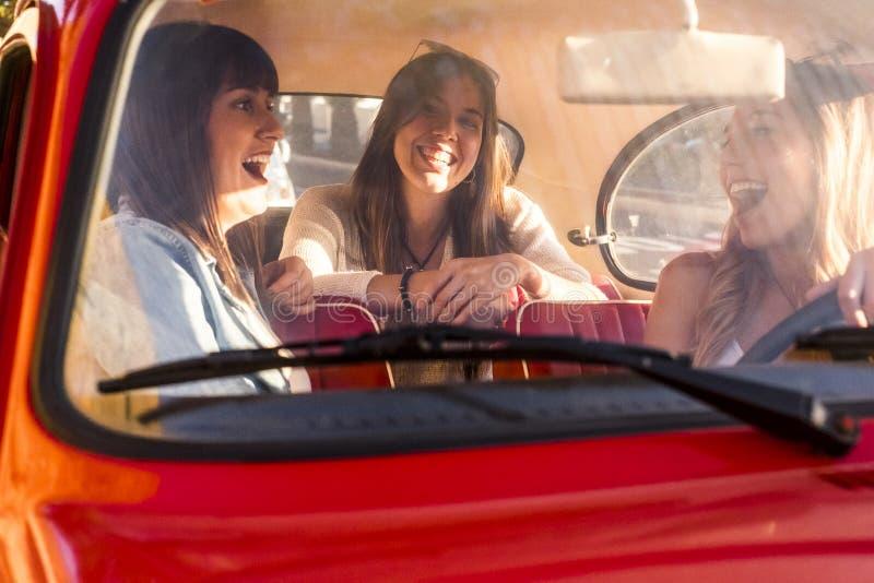 Gruppe junge Freundinnen innerhalb eines alten roten Autos stockbilder