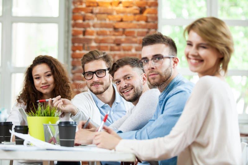 Gruppe junge gemischtrassige Leute, die im modernen hellen Büro arbeiten Geschäftsmänner bei der Arbeit während der Sitzung lizenzfreies stockbild