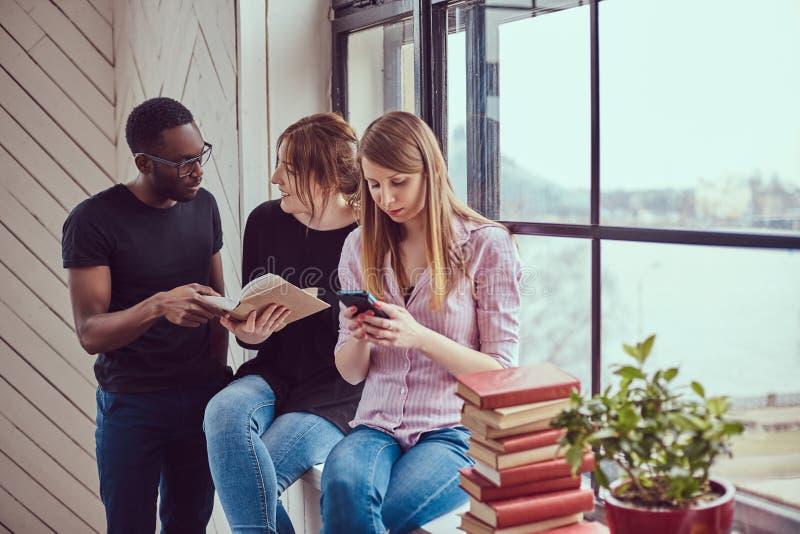 Gruppe junge gemischtrassige Studenten, die mit Büchern und Telefon arbeiten stockfoto