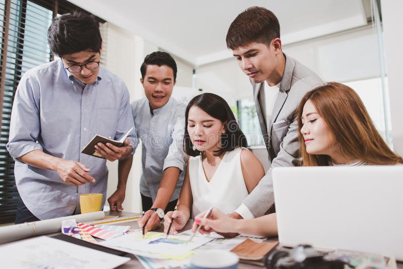 Gruppe junge Geschäftsleute, die an einem Schreibtisch arbeiten lizenzfreie stockfotografie