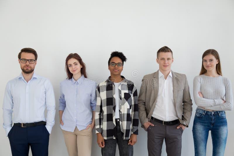 Gruppe junge Geschäftsleute, die Kamera betrachtend stehen stockfoto