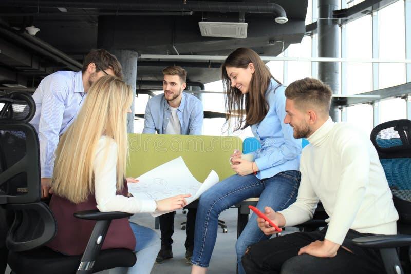 Gruppe junge Geschäftsleute und Designer in der intelligenten Freizeitkleidung Sie arbeitend an neuem Projekt lizenzfreie stockfotos