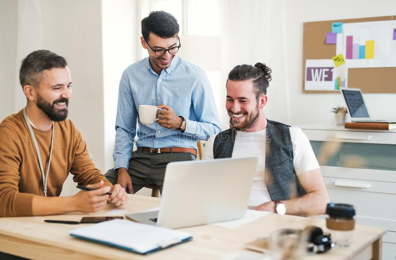 Gruppe junge Geschäftsmänner mit Laptopfunktion in einem modernen Büro stockbild