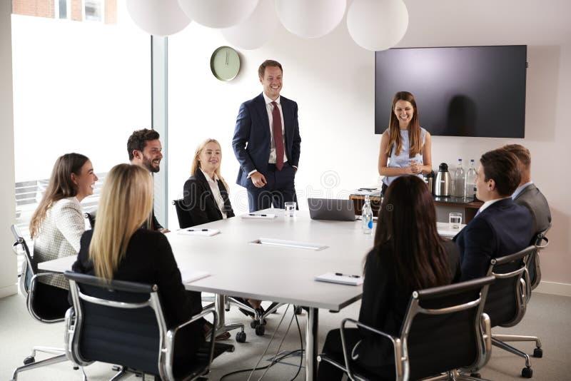 Gruppe junge Geschäftsmänner und Geschäftsfrauen, die um Tabelle am graduierten Einstellungs-Einschätzungs-Tag sich treffen stockbild