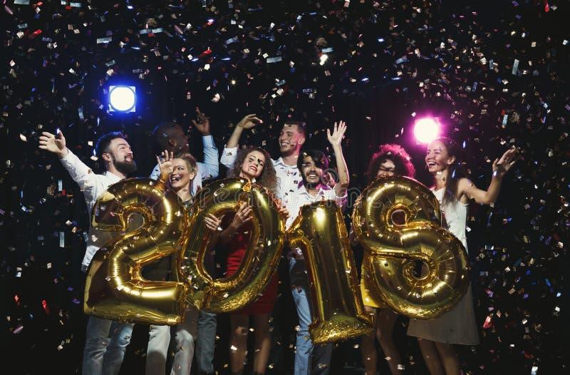 Gruppe junge glückliche Freunde mit Zahl steigt an der Partei des neuen Jahres im Ballon auf stockbild