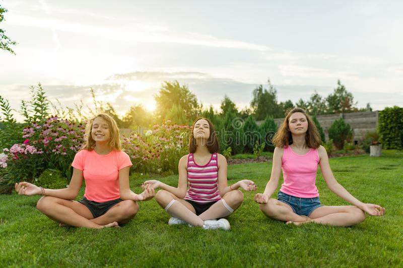 Gruppe junge Jugendlichen üben Yoga, meditieren, sitzen in einem Lotussitz auf dem Gras nahe dem Haus stockfoto