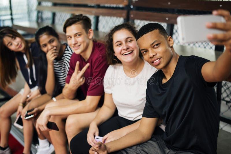 Gruppe junge Jugendlichfreunde auf einem Basketballplatz, der ein selfie nehmend sich entspannt lizenzfreies stockbild