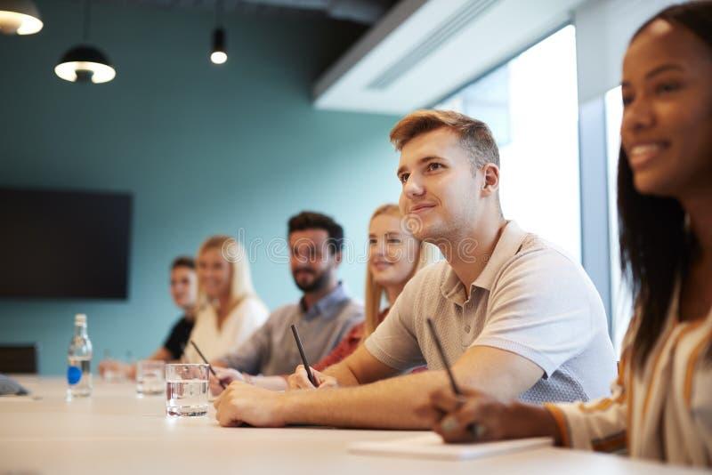Gruppe junge Kandidaten, die am Sitzungssaal-Tisch hörend auf Darstellung Geschäfts-am graduierten Einstellungs-Einschätzungs-Tag lizenzfreie stockfotografie