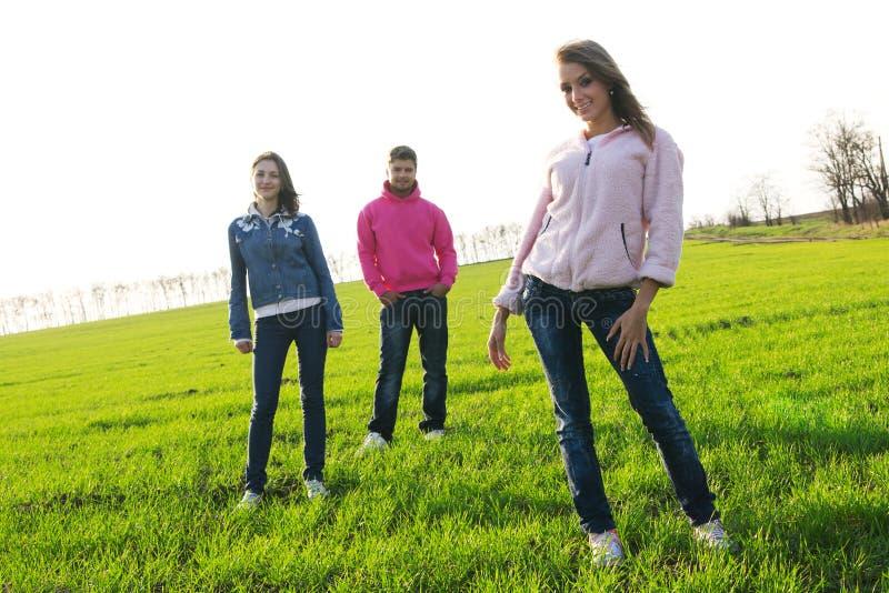 Gruppe junge Leute auf einem grünen Feld lizenzfreie stockbilder