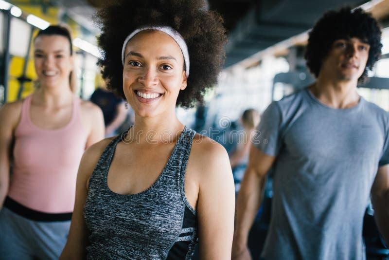Gruppe junge Leute, die Übungen im Fitness-Club tun lizenzfreie stockbilder