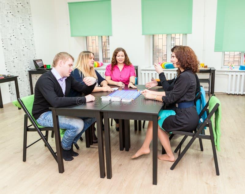 Gruppe junge Leute, die bei Tisch sitzen und Spiele spielen lizenzfreies stockfoto
