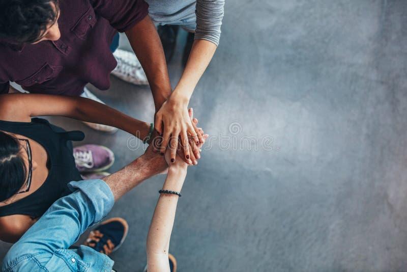 Gruppe junge Leute, die ihre Hände stapeln stockfoto