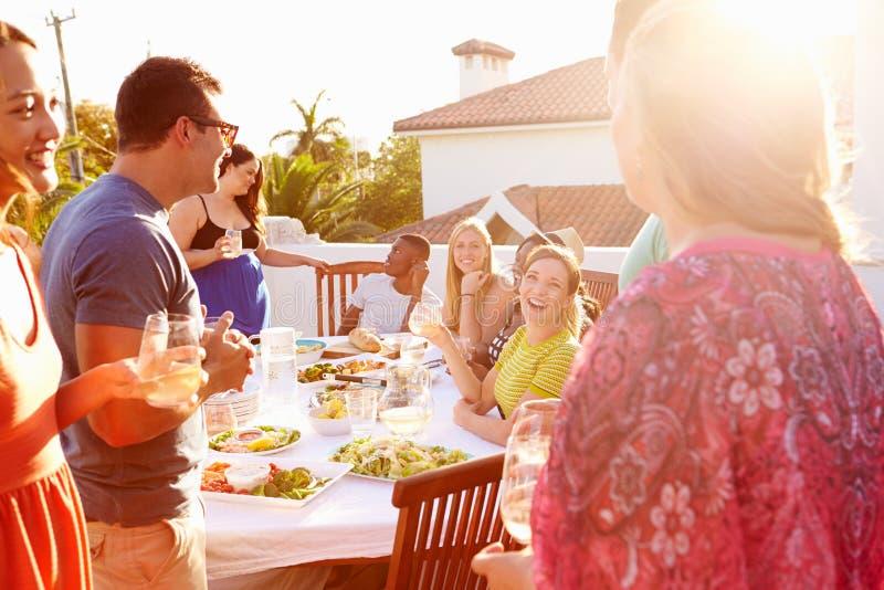 Gruppe junge Leute, die Sommer-Mahlzeit im Freien genießen stockfotografie