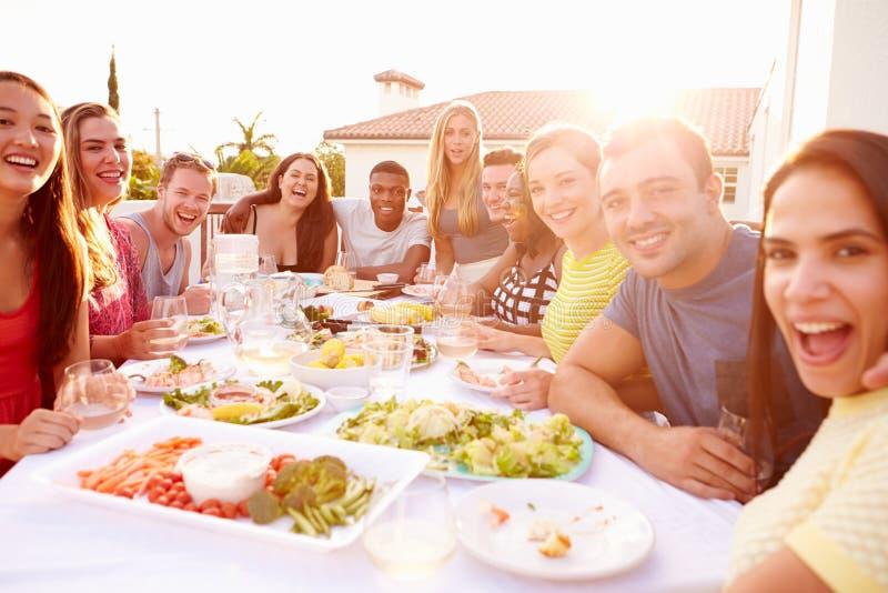 Gruppe junge Leute, die Sommer-Mahlzeit im Freien genießen lizenzfreie stockbilder