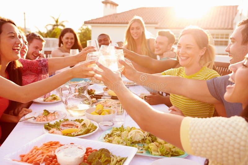 Gruppe junge Leute, die Sommer-Mahlzeit im Freien genießen stockfoto