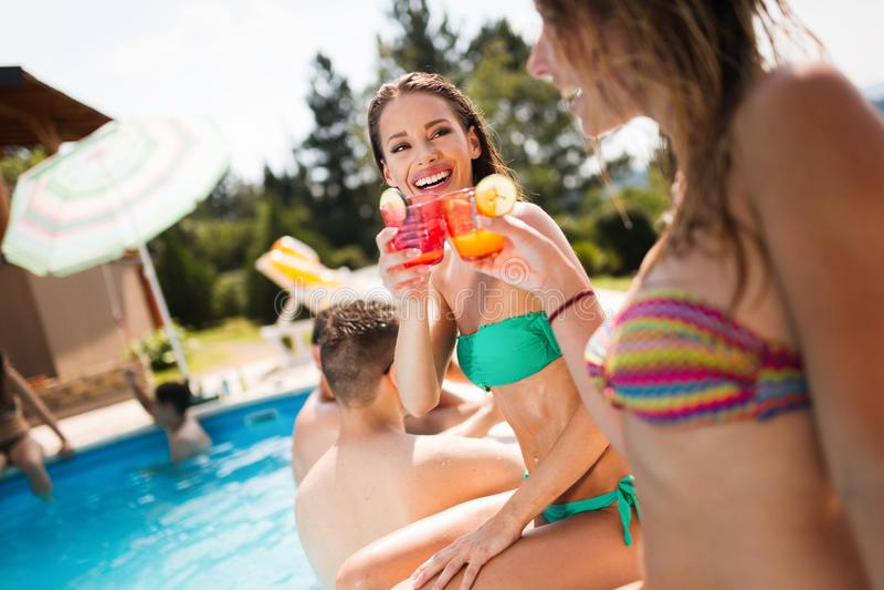 Gruppe junge Leute, die Sommer am Pool genießen lizenzfreie stockfotos