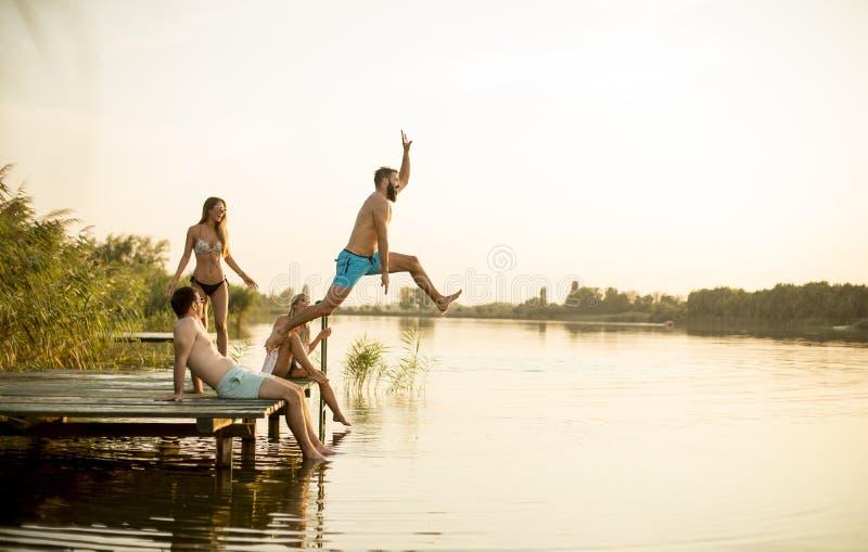 Gruppe junge Leute, die Spaß auf Pier am See haben lizenzfreie stockbilder