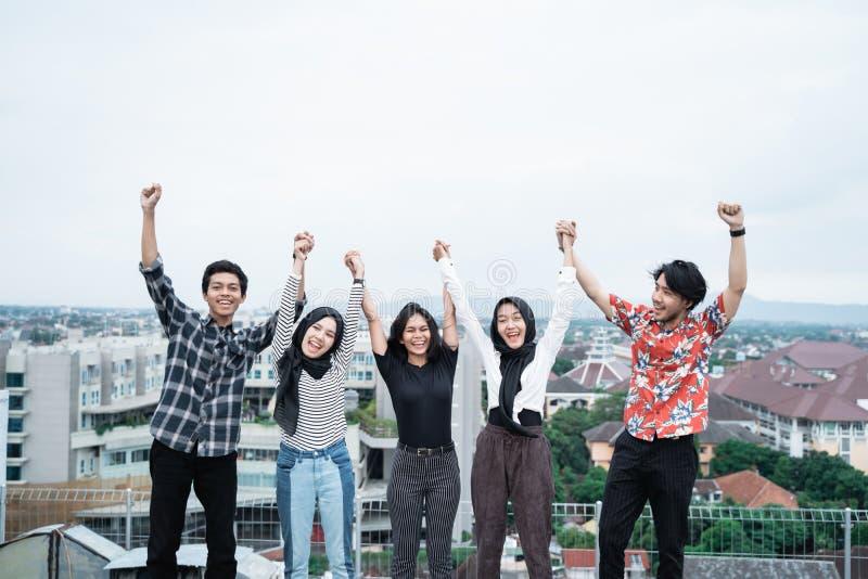 Gruppe junge Leute, die Spaß an einer Dachspitze haben lizenzfreie stockbilder