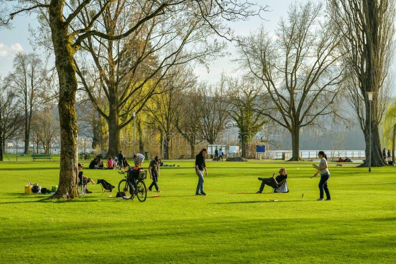 Gruppe junge Leute, die Spiel im kleinen Park an den Ufern von Luzerner See in Luzern spielen stockbild