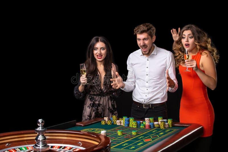 Gruppe junge Leute, die spinnenden Rouletten aufgeregt betrachten stockbild