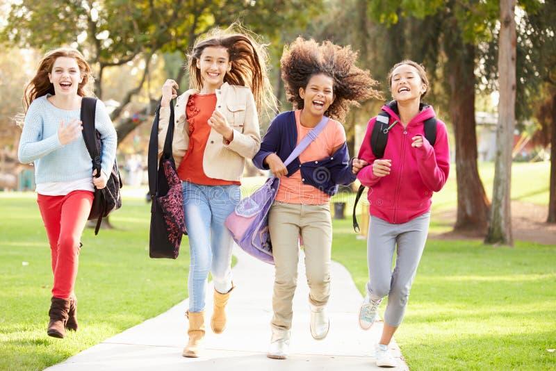 Gruppe junge Mädchen, die in Richtung zur Kamera im Park laufen stockfotografie