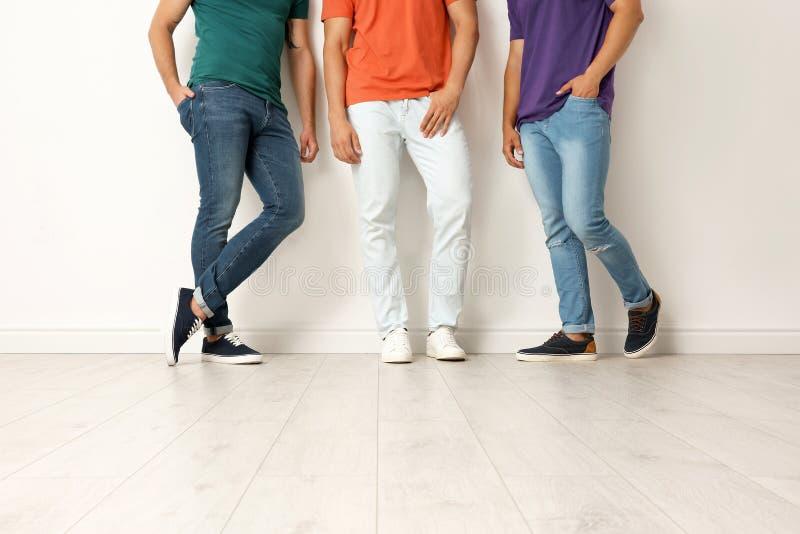 Gruppe junge Männer in den Jeans und in den bunten T-Shirts stockfotografie
