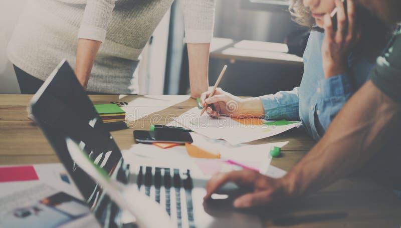 Gruppe junge Mitarbeiter, die im modernen coworking Studio zusammenarbeiten Frau, die den Smartphone spricht mit Partnern verwend lizenzfreie stockfotografie