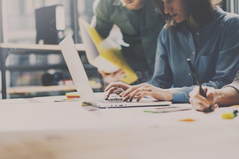 Gruppe junge Mitarbeiter, die im modernen coworking Studio zusammenarbeiten Frau, die Laptop verwendet und mit Kollegen ungefähr  lizenzfreie stockbilder