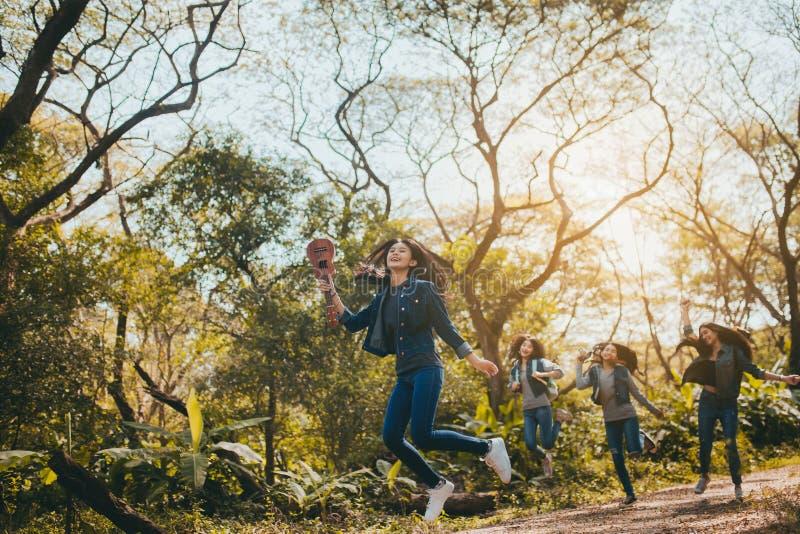 Gruppe junge springende Asiatinnen, Reisetrekking zu genießen lizenzfreie stockbilder