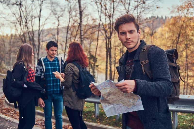 Gruppe junge Wanderer, die auf den Straßennebenerwerben am schönen Herbstwald, Kerl mit Kartenplanungswanderung stehen lizenzfreies stockfoto