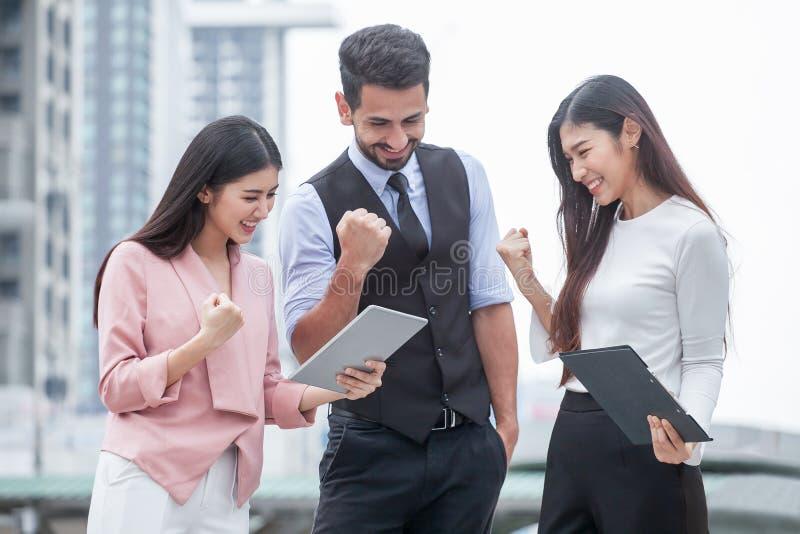 Gruppe junger Mann und Freundinnen, die eine Tablette verwenden und drau?en lachen drei Leute aufregendes Gesch?ft der Teamwork o lizenzfreie stockbilder