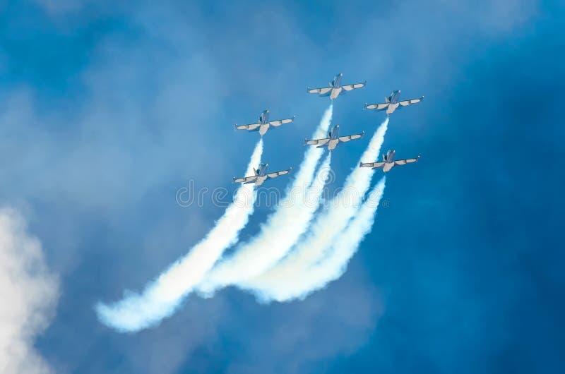 Gruppe Kampfflugzeugflugzeuge fliegen und verlassen hinter einer weißen Rauchspur stockbilder