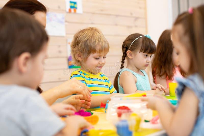 Gruppe Kinder auf Kunstunterrichten mit Lehrer im Kindergarten stockfoto