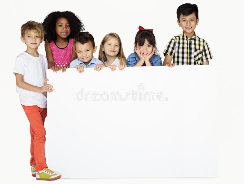 Gruppe Kinder, die Copyspace-Brett zeigen stockfotografie