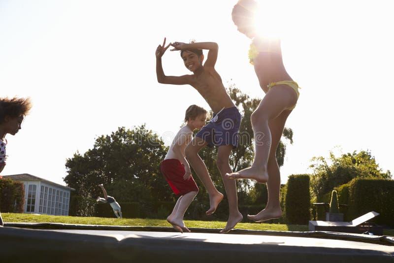 Gruppe Kinder, die den Spaß springt auf Trampoline im Freien haben stockfotografie
